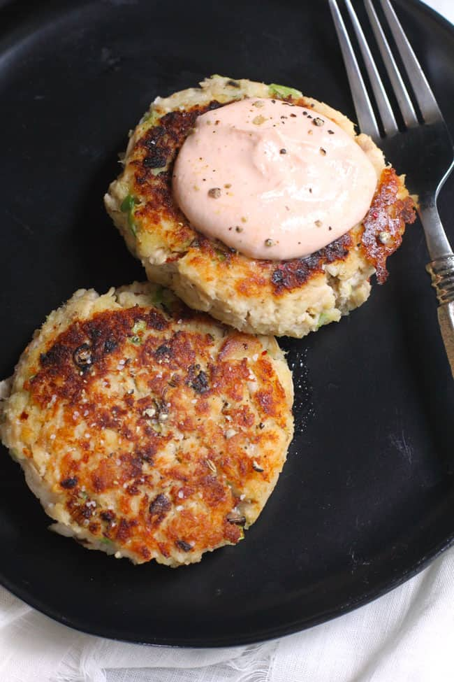 Overhead shot of two tuna patties, on a black plate, one with some sriracha dip on top.