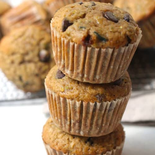 Side shot of a stack of three zucchini muffins, with more muffins in the background.