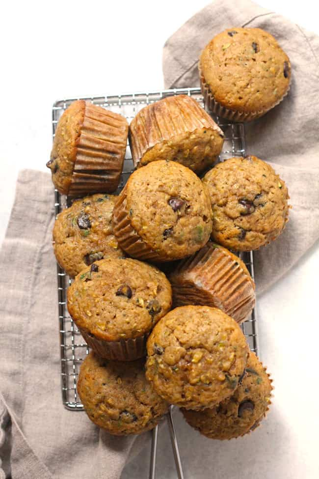 Overhead shot of a pile of zucchini muffins, on a rectangular wire rack, with a gray napkin.