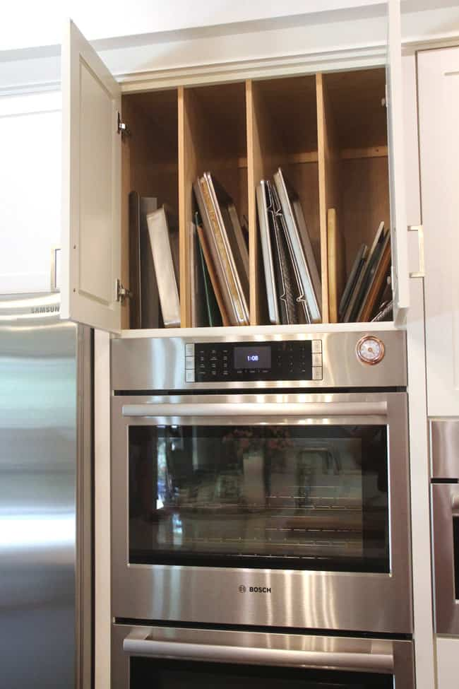 Open cabinet above ovens showing sheet pans.