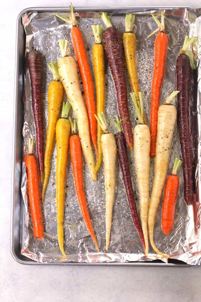 Overhead shot of a bunch of multi-colored carrots on a baking sheet, seasoned for baking.