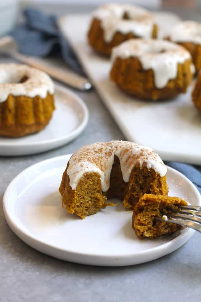 Side shot of a partially eaten pumpkin bundt cake with others in the background.