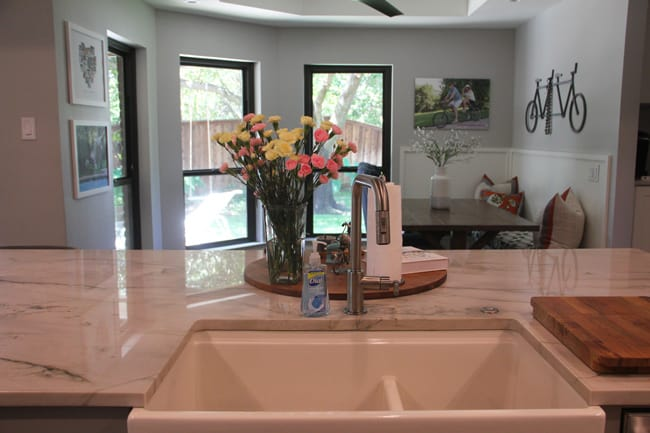A shot of the sink with the kitchen seating table in the background.