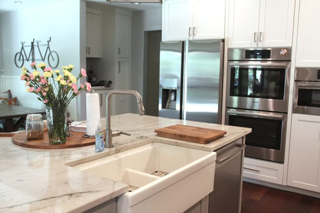 A shot of the farmhouse style sink and the appliances wall in the background.