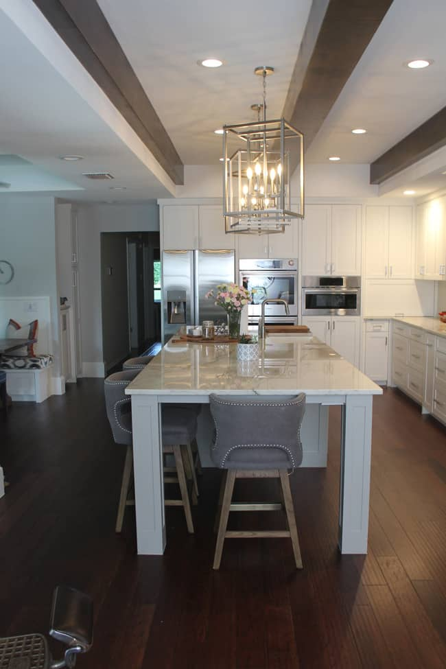 A shot of the large kitchen island and beams overhead.