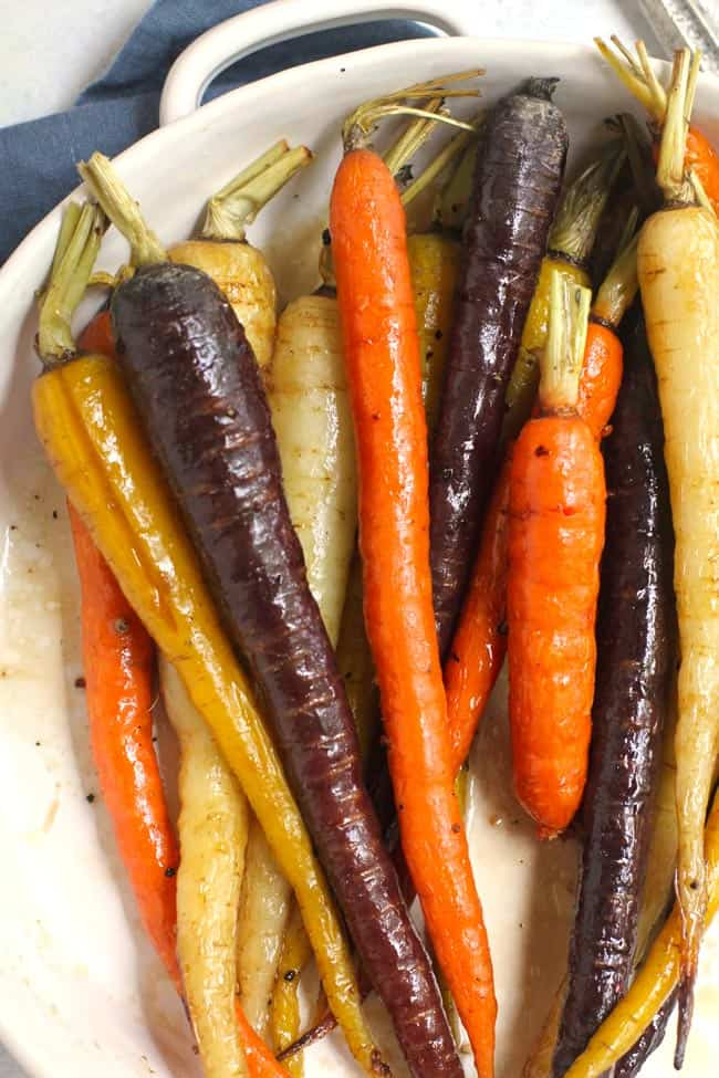 Close-up shot of a round white dish filled with whole multi-colored roasted carrots.