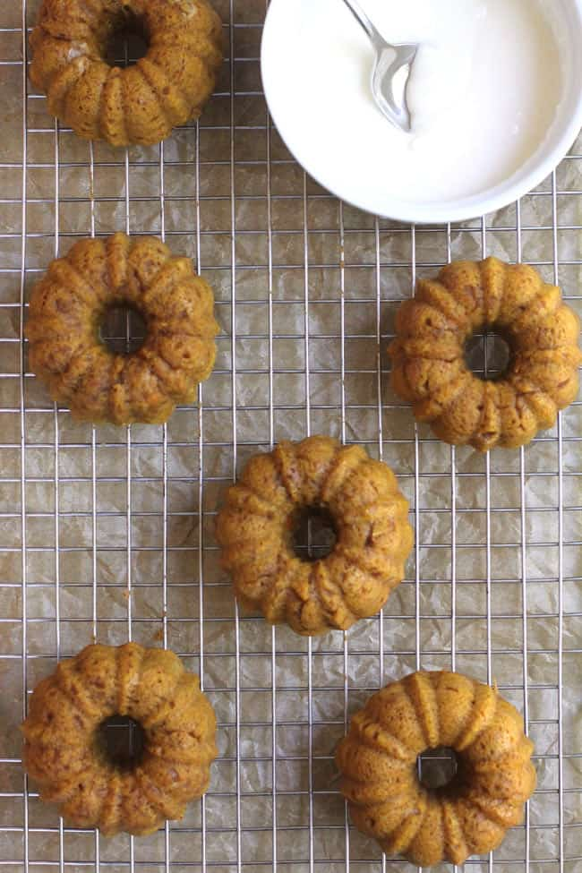 Overhead shot of six mini pumpkin bundt cakes on a wire rack, with a bowl of icing in a. white bowl.