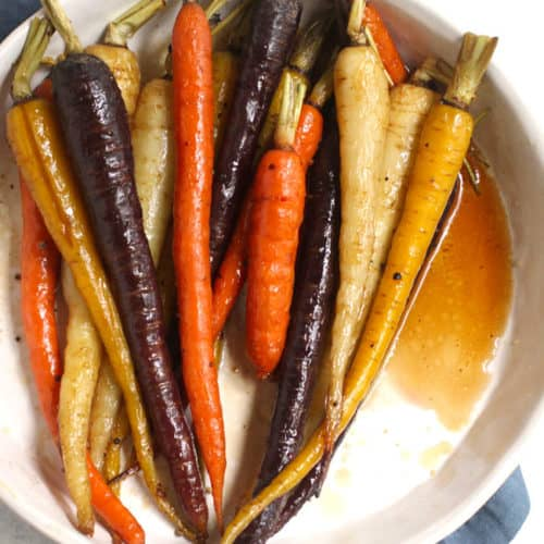 Overhead shot of a round white dish filled with whole multi-colored roasted carrots, on a blue napkin.
