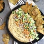 Overhead shot of a plate of hummus with cucumbers and onions, and pita chips, on a gray background.