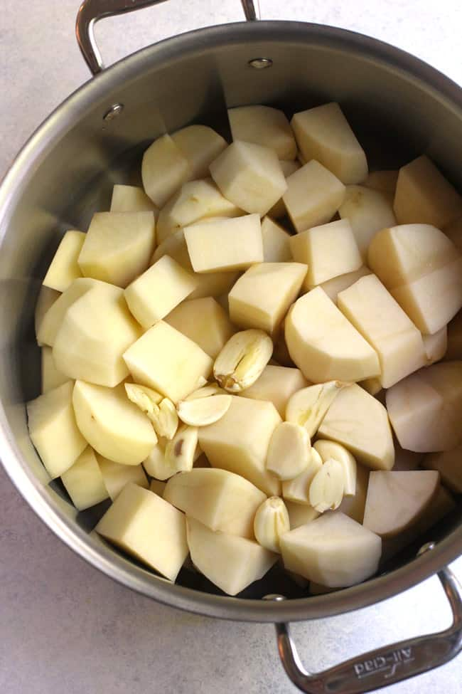 Overhead shot of a large stock pot filled with raw potato chunks and garlic cloves.