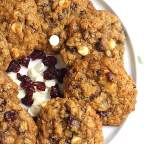 Overhead shot of a white plate of white chocolate cranberry oatmeal cookies.