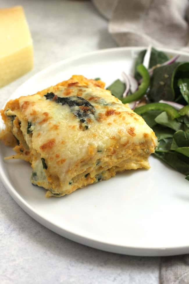 Side dish of a plate of butternut squash lasagna with greens.