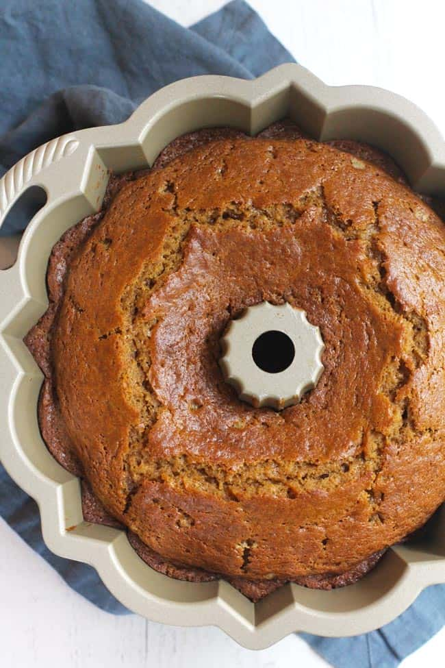 Overhead shot of a baked pumpkin streusel cake in a bundt pan, on a gray background.