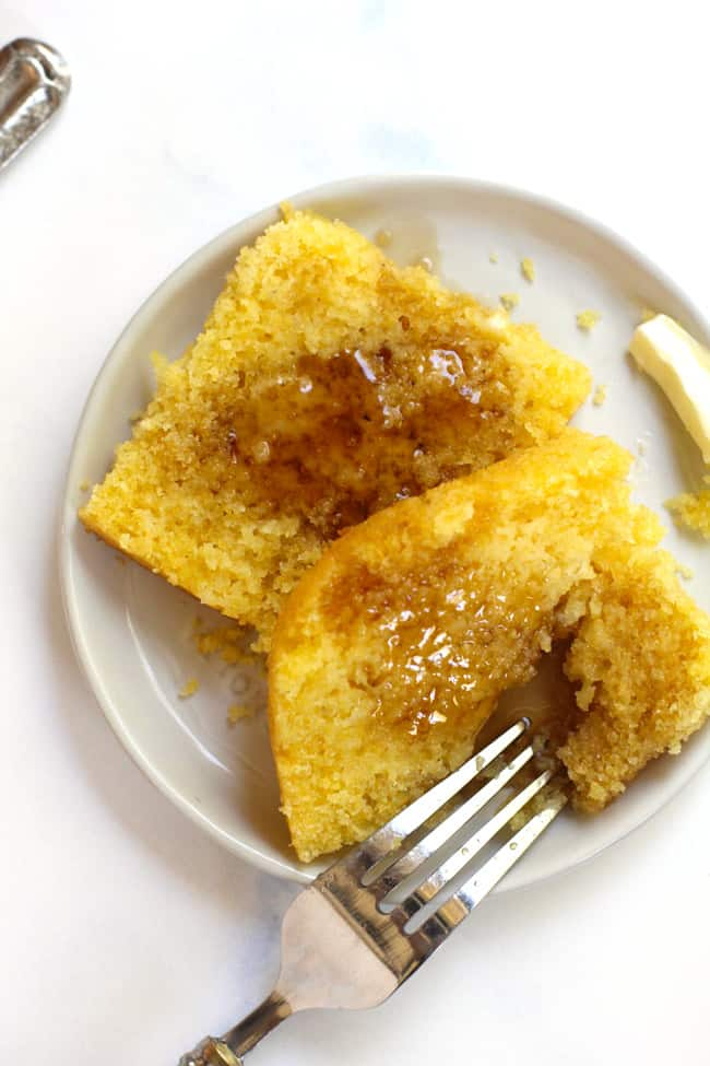 Overhead shot of a sliced open piece of cornbread on a white plate, with butter and syrup on top.