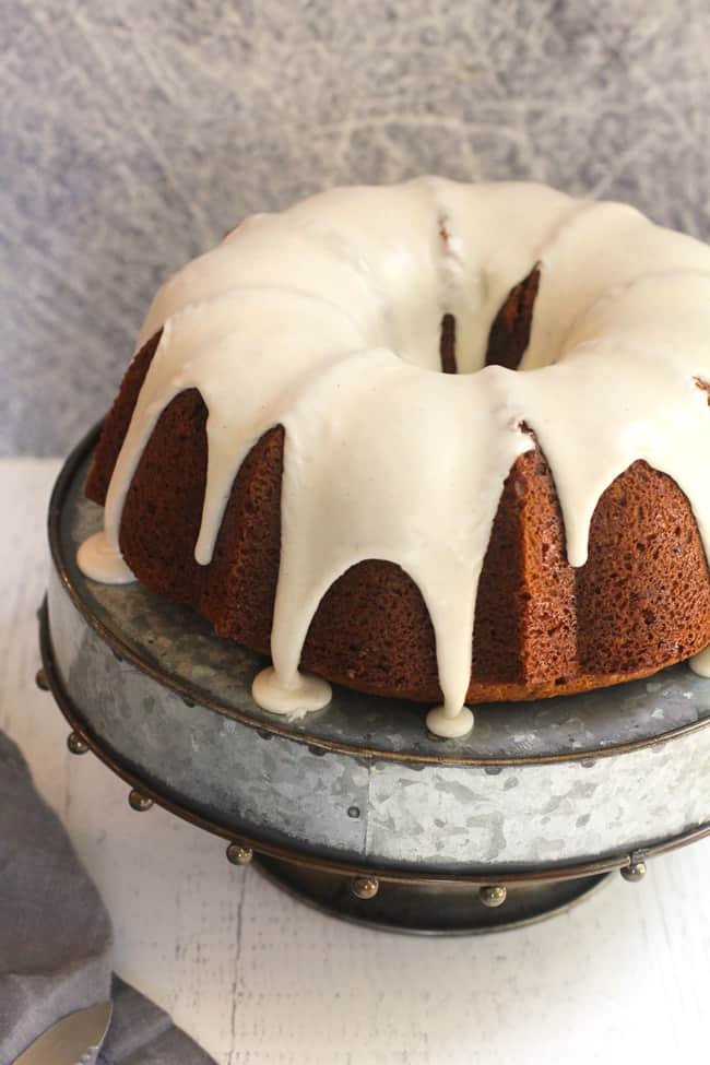 Side shot of an iced pumpkin streusel cake, on a silver cake plate.