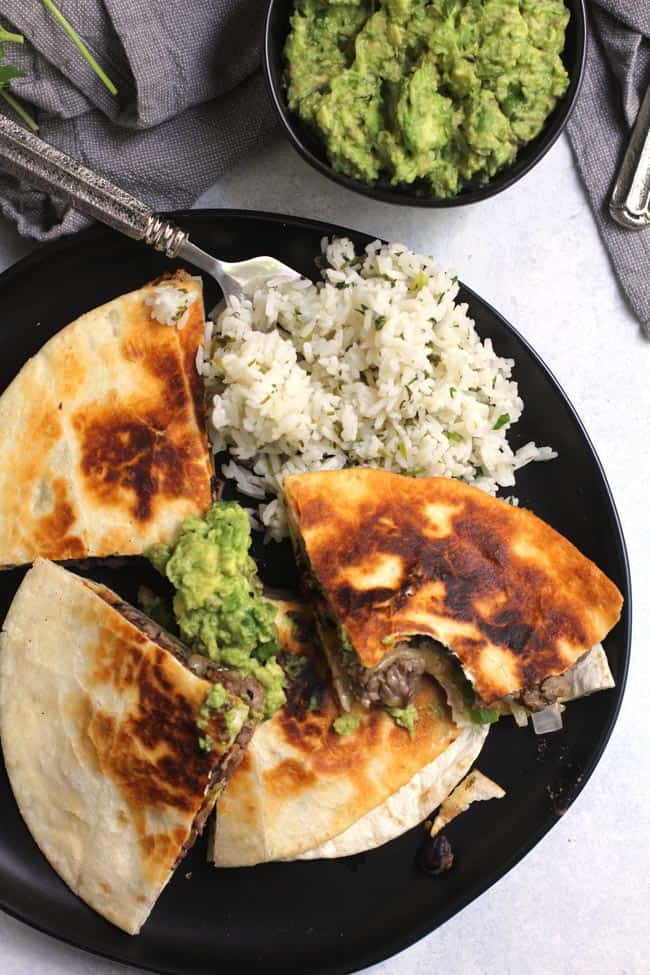Overhead shot of a plate of steak fajita quesadillas, with a side of guac and a side of cilantro lime rice.