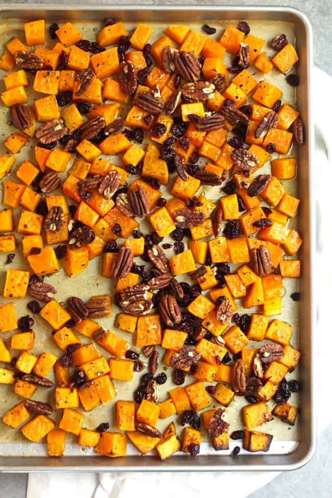 Overhead shot of a sheet pan of roasted butternut squash with pecans and cranberries.