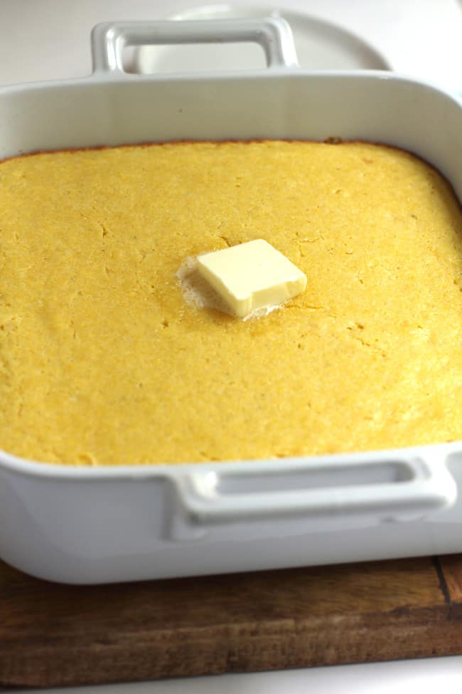 Side shot of a square white dish of cornbread, with a dollop of butter in the middle of it.