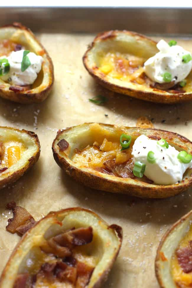 Side shot of several crispy potato skins, loaded with bacon, cheese, and sour cream.