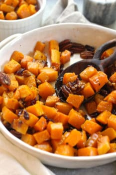 Side shot of a white dish of roasted butternut squash with pecans and cranberries, with a wooden spoon it it.