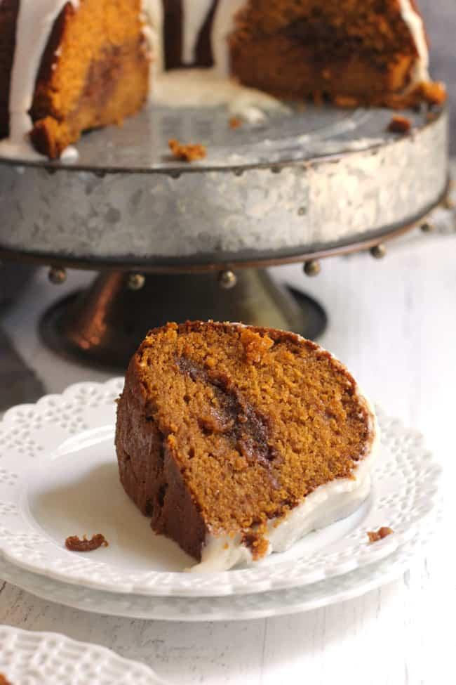 Side shot of the inside of a pumpkin streusel Cake on a gray cake plate, with a large slice of cake in front.