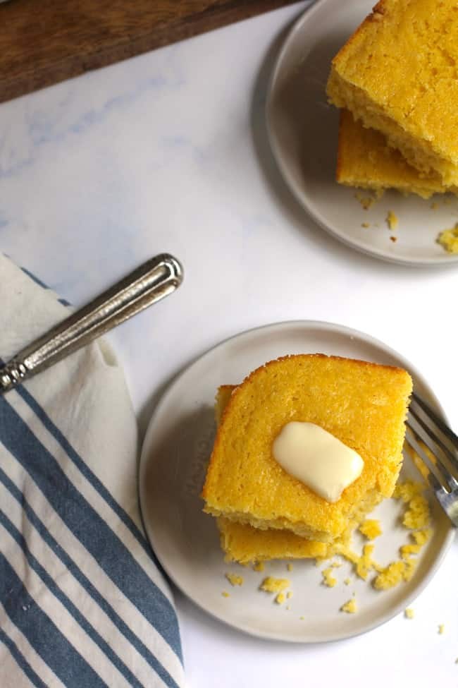 Overhead shot of two plates of a double stack of cornbread, with butter on top.