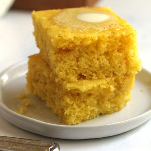 Side shot of two stacked pieces of cornbread on a white plate, with a dollop of melting butter on top.