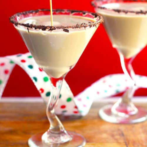Side shot of two chocolate martinis, with chocolate shavings lining the rims, and a drizzle of martini being poured into one, all with a red background.