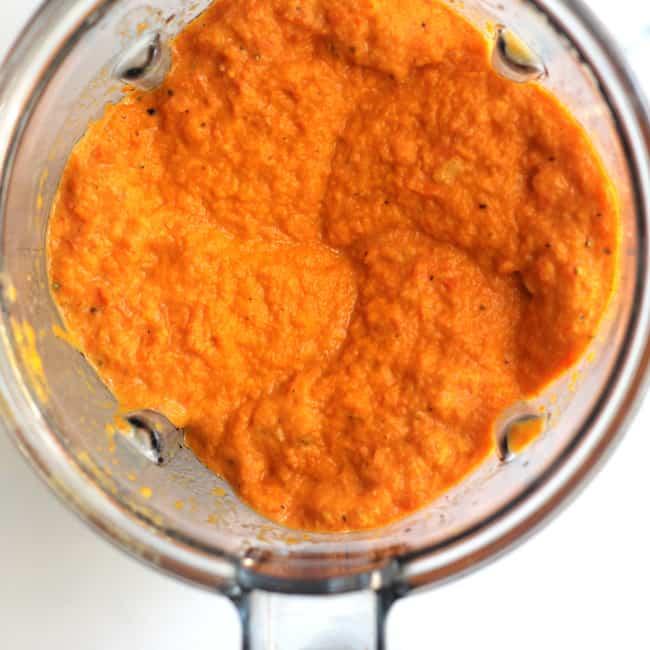 Overhead shot of a blender full of roasted carrot soup.