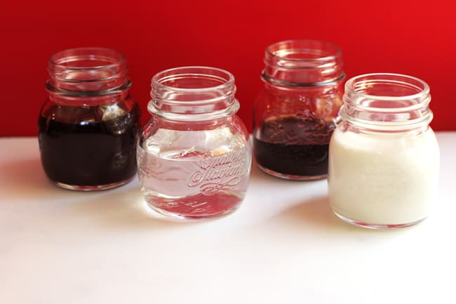 Side shot of four small jars filled with the liquors and the half and half for chocolate martinis.