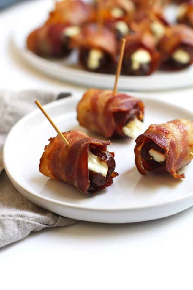 Side shot of a small plate of three bacon wrapped dates, with a larger plate in the distance.