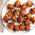 A white round plate of bacon wrapped dates with goat cheese, secured with toothpicks.