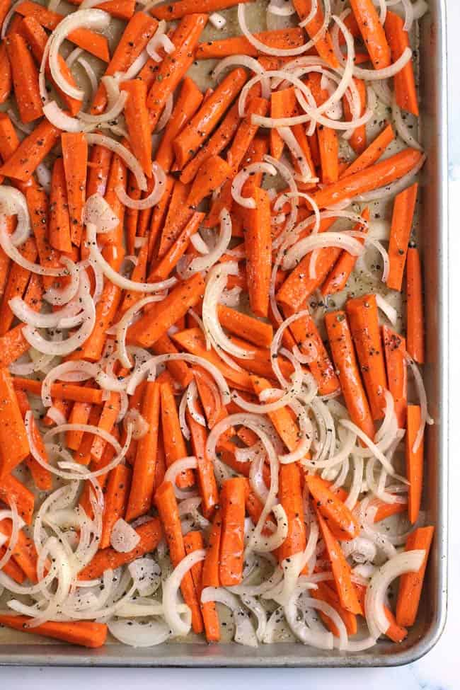A sheet pan of sliced carrots and onions, ready for roasting in the oven.