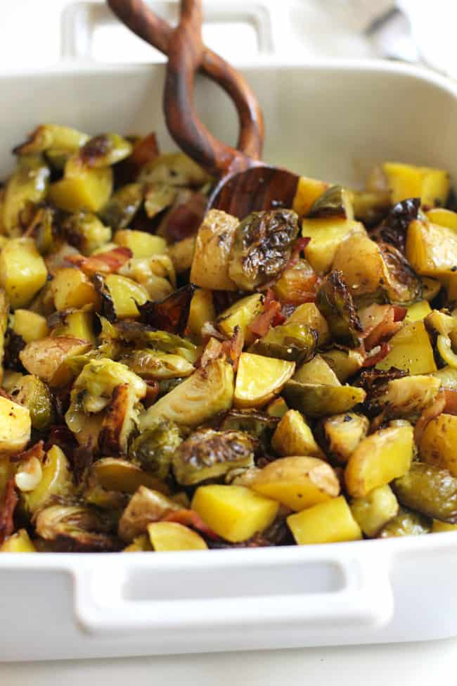 Side shot of a dish of roasted potatoes and Brussels sprouts, with a wooden spoon.