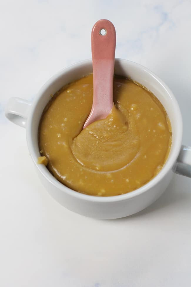 The caramel frosting in a round white bowl, with a pink spoon inside.