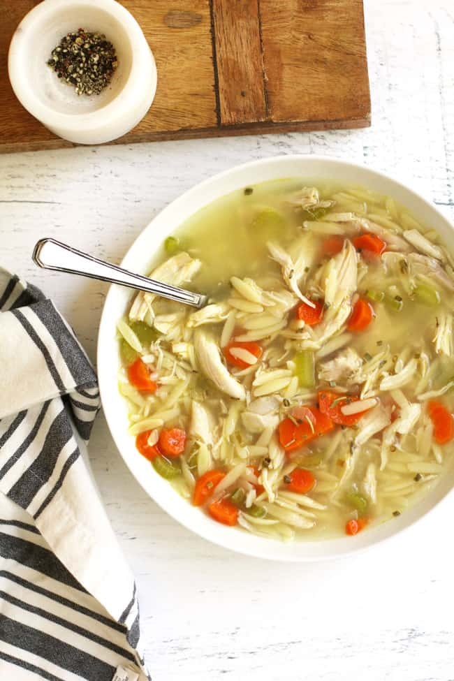 Overhead shot of a large bowl of lemon chicken orzo soup, with a gray and white napkin.