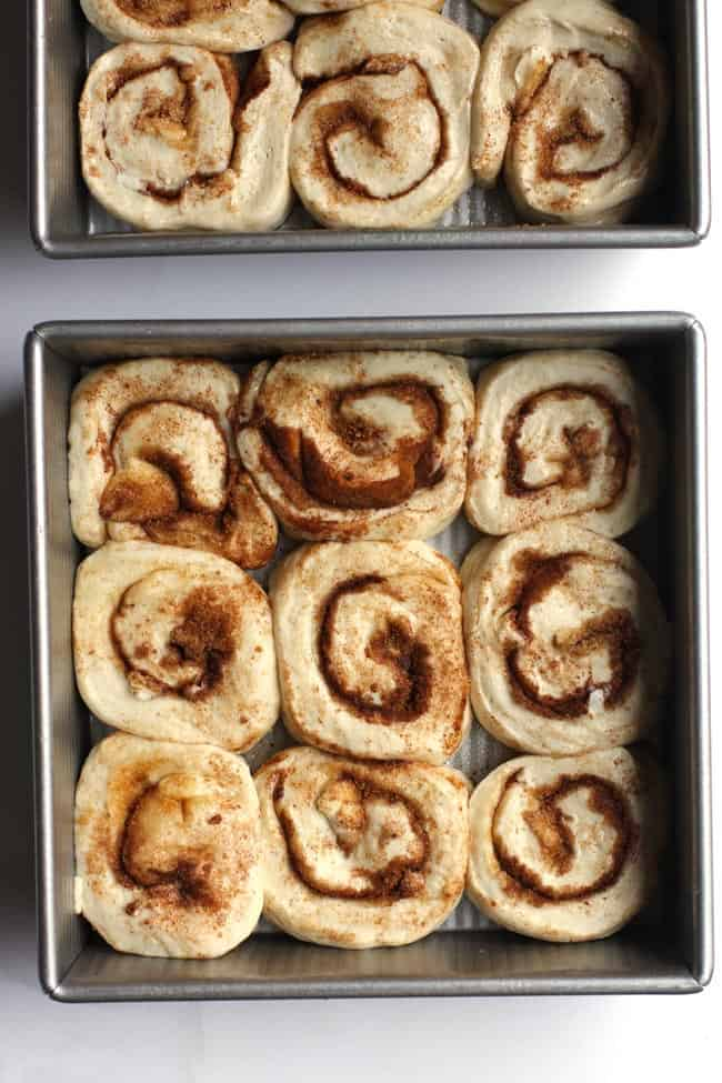Overhead shot of the cinnamon roll dough arranged in USA square pans.