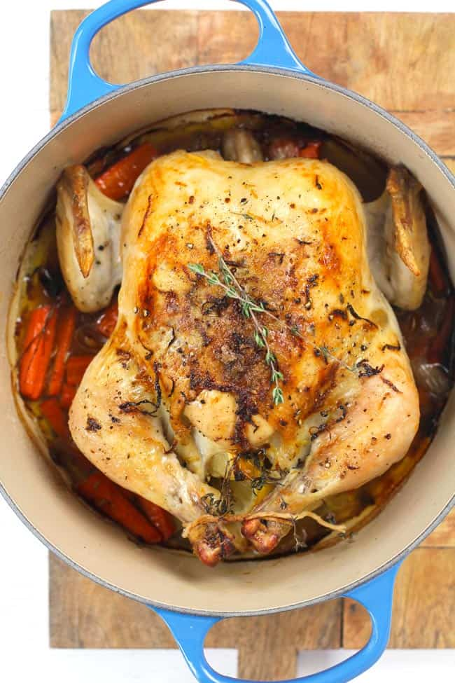 Overhead shot of a whole roasted chicken in a blue pot with carrots and onions.