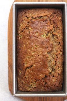 Overhead shot of a loaf of zucchini bread in a loaf pan, on a wooden board.