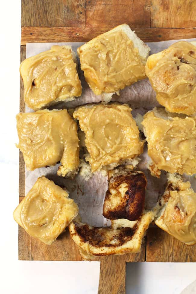 Overhead shot of cinnamon rolls with caramel frosting, on a wooden board with white parchment, showing all nine rolls pulled apart.