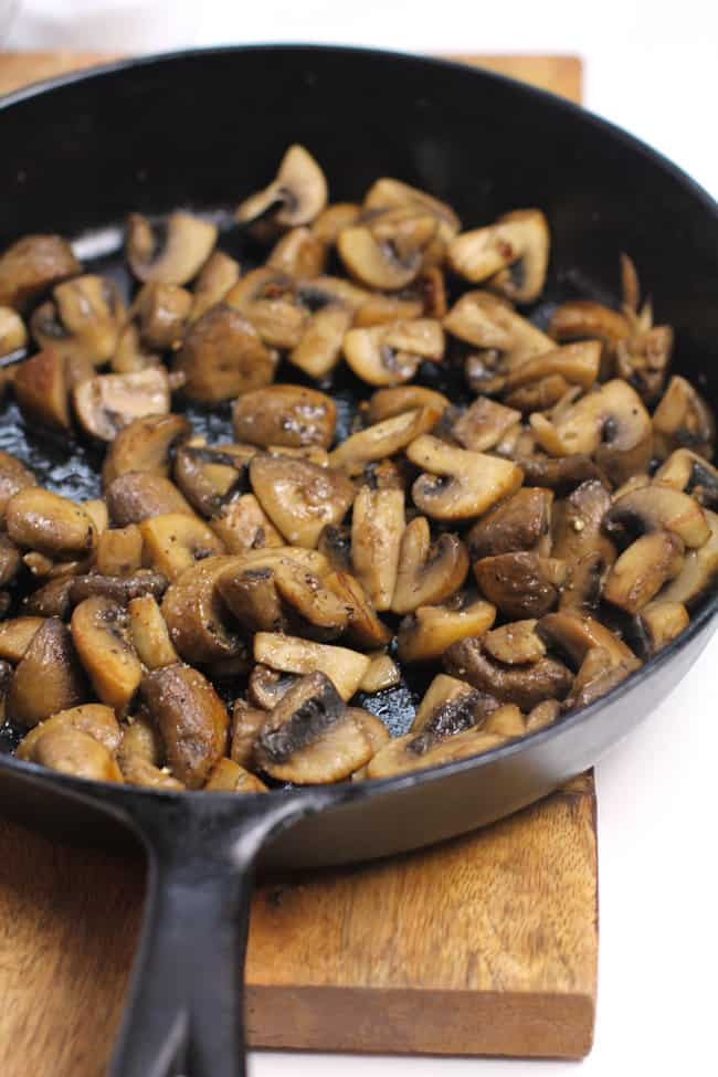 Side shot of a cast iron skillet full of browned mushrooms.