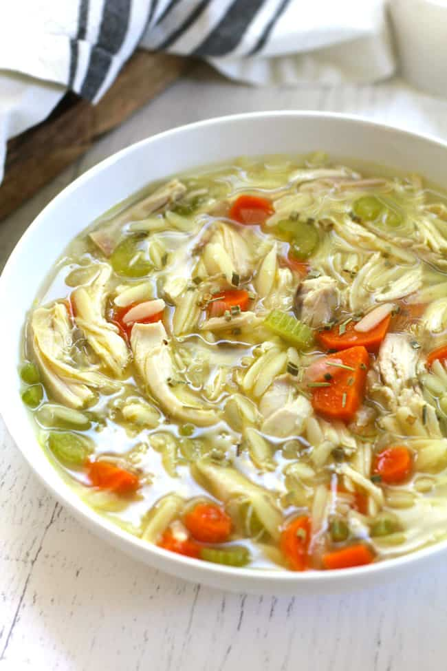 Side shot of a white bowl of lemon chicken orzo soup.