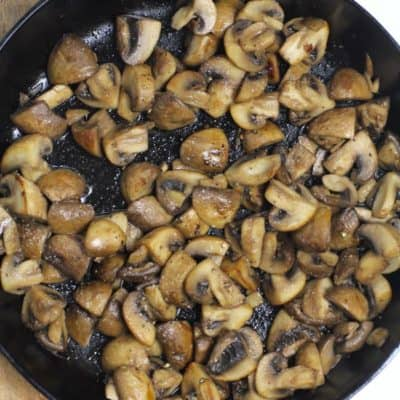 Overhead shot of a cast iron skillet filled with browned mushrooms.