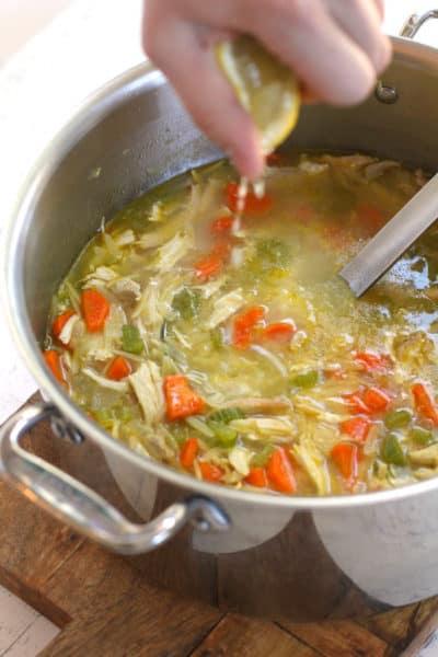 A hand squeezing lemon into a pot of chicken orzo soup.