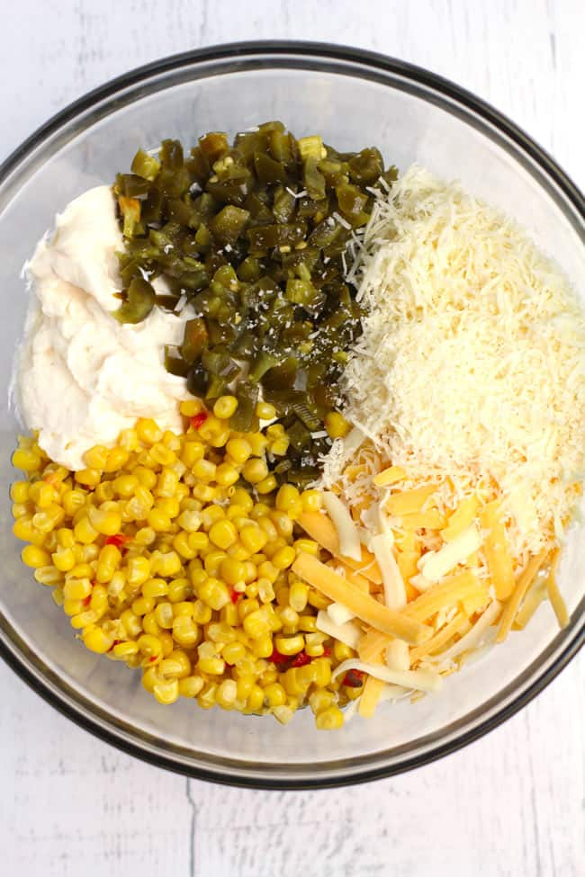 Overhead shot of a glass bowl filled with crazy good corn dip ingredients, separated by ingredient, on a white background.