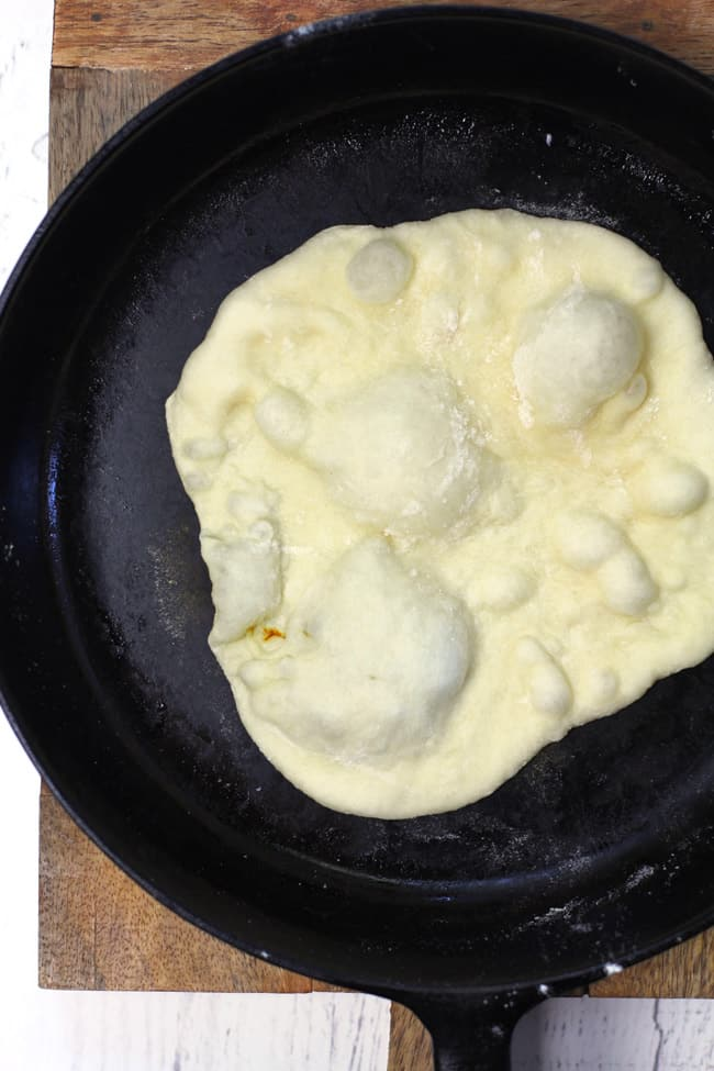 A cast iron skillet with a naan bread inside with bubbles, before flipping.