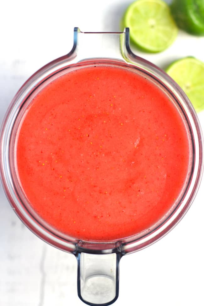 Overhead shot of a pitcher of frozen strawberry lemonade margaritas, with some lime wedges next to it.