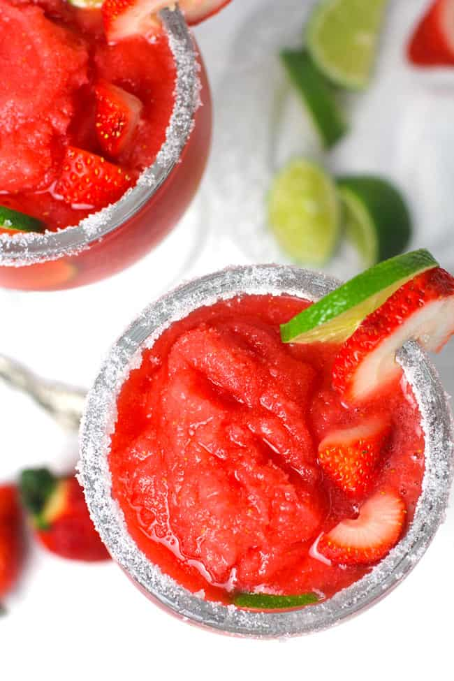 Overhead shot of two frozen strawberry lemonade margaritas, with a salt rim, and lime and strawberry wedges on the glass.