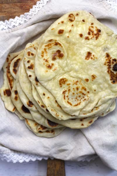 Overhead shot of a stack of naan bread, freshly grilled, on a beige napkin.