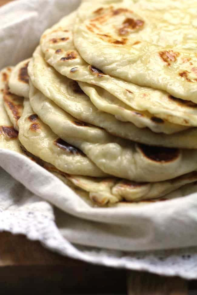 Side angle of a stack of soft, pillowy homemade naan bread.